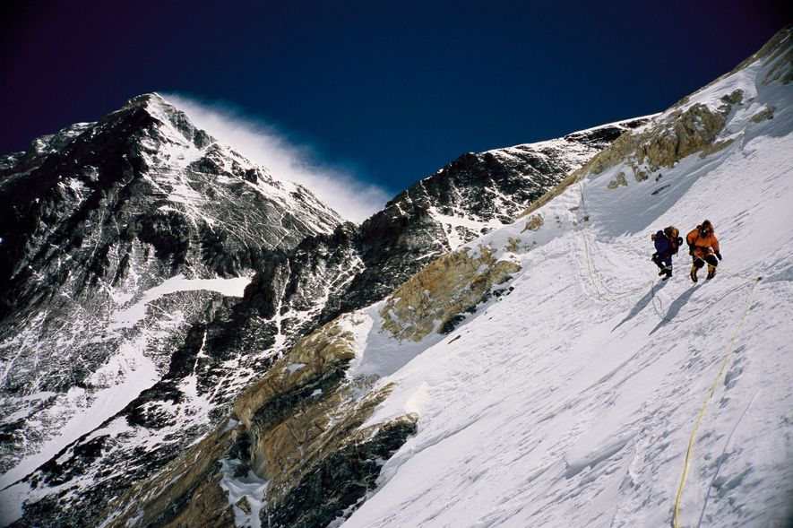 Climbers approach the summit of Mount Everest. There are plumes of clouds blowing off the summit, ...