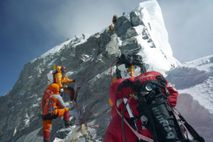 Mountaineers walk past the Hillary Step while pushing for the summit of Mount Everest as they ...