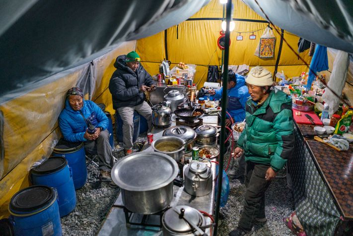 After the dinner rush, the cooking crew relaxes with visitors. Nepali cook Bire Tamang (back right) ...