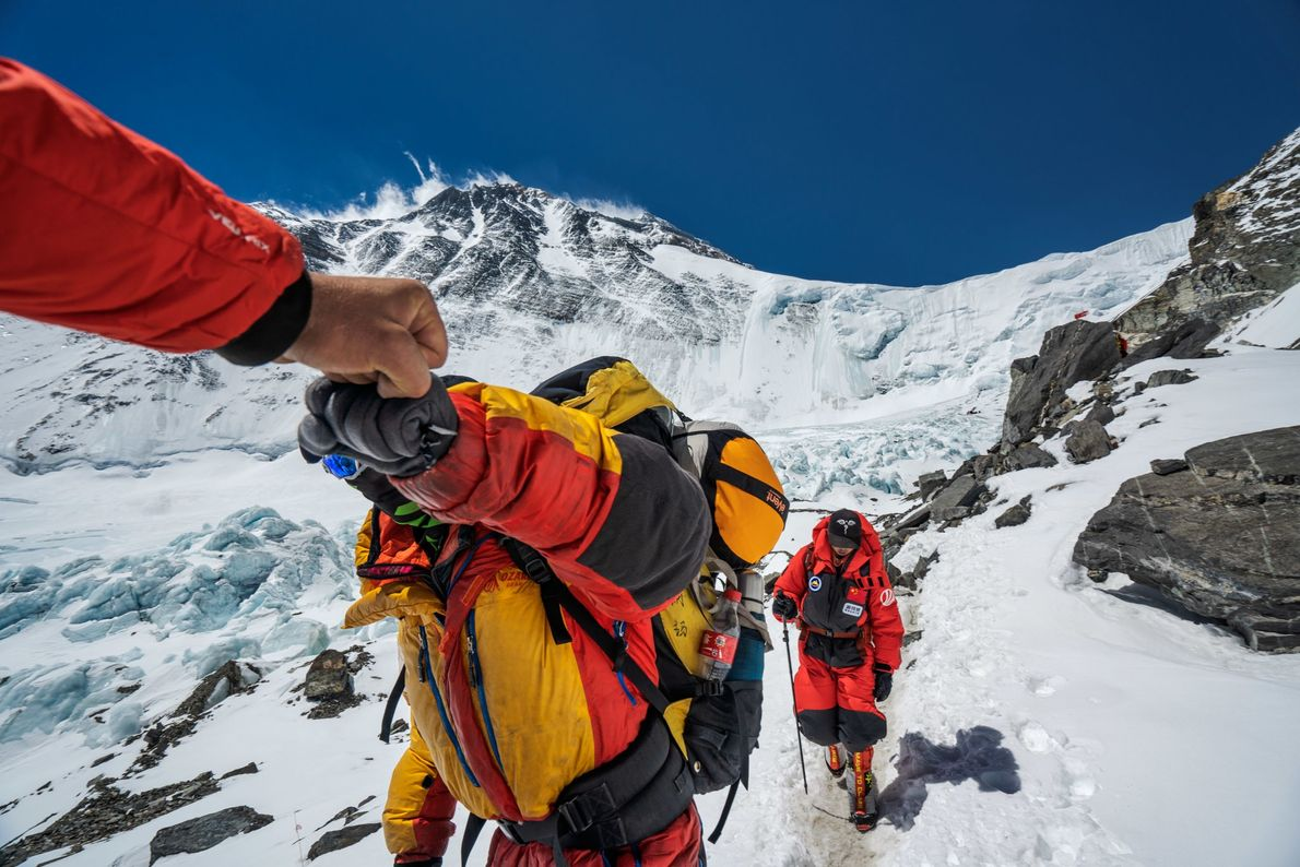 Photographer Renan Ozturk fist-bumps a climber returning to Advanced Base Camp.