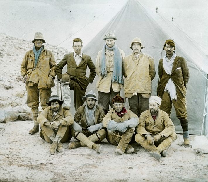 In this hand-tinted image, a smiling Irvine (at far left) stands next to Mallory, who rests ...