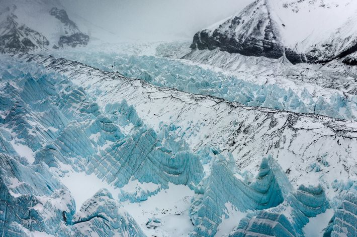 Snow dusts the rocky Miracle Highway on the East Rongbuk Glacier as a group of climbers ...