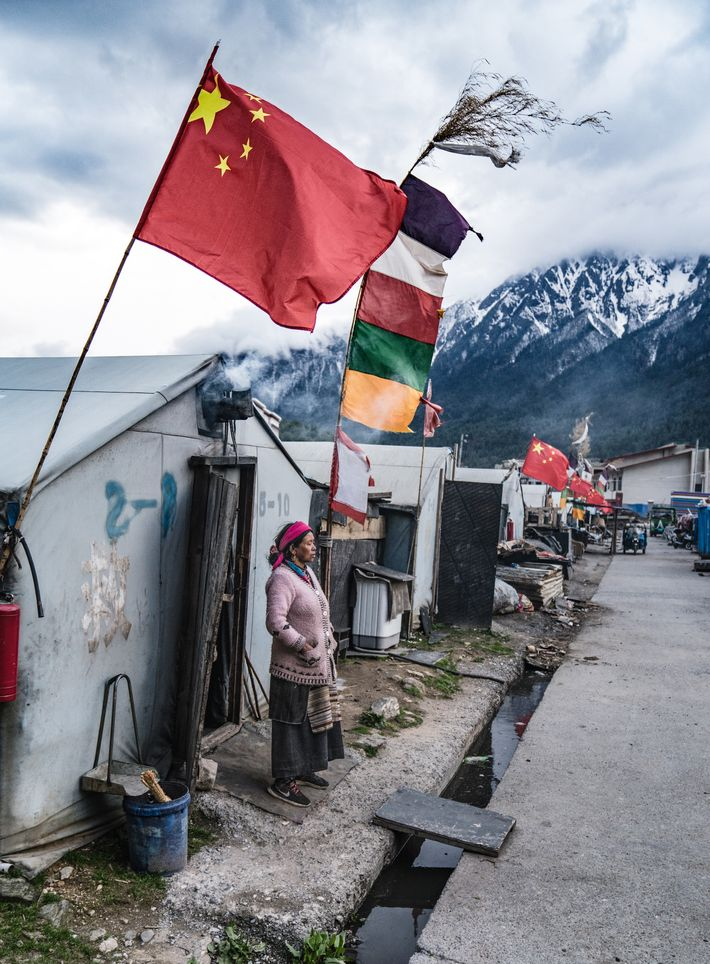 The Chinese flag flies side by side with Tibetan prayer flag colours in the mountain village ...