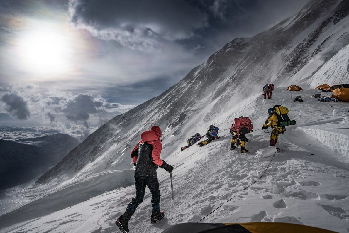 Jim Hurst, the film team's sound engineer, races toward a group of Indian climbers who were ...