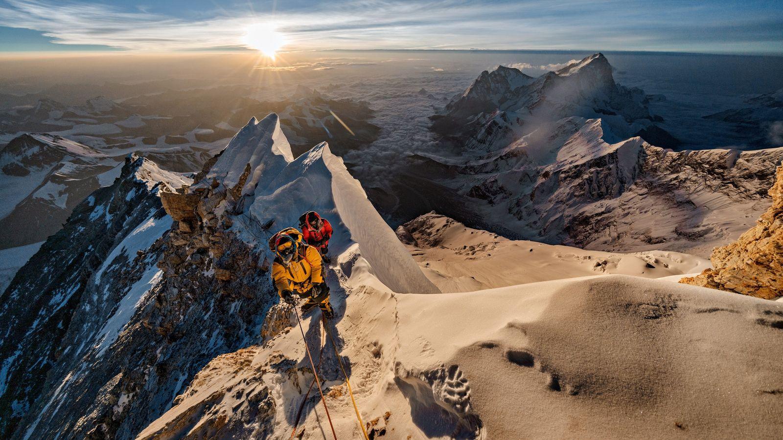 The sun illuminates the Tibetan plateau, shining its light on the northern flanks of Everest. The ...