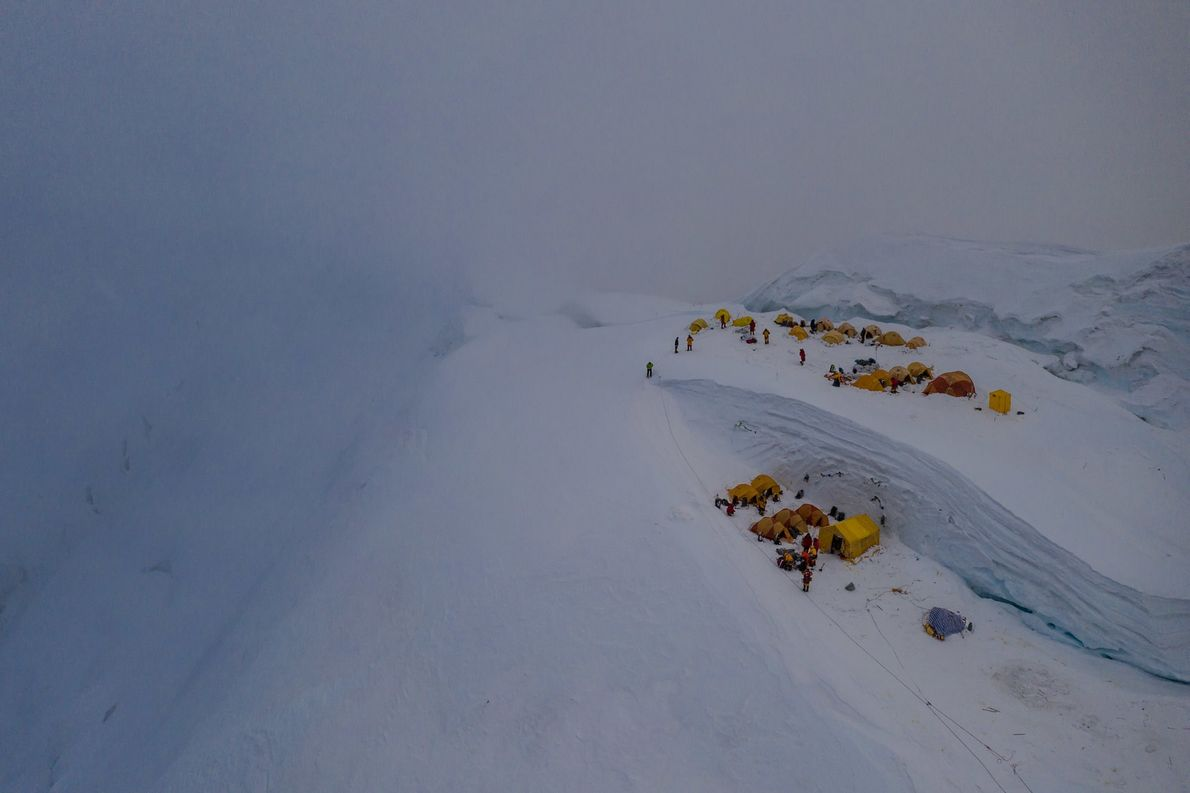 Just before a storm, tents from several expeditions huddle against the snowy slope in this drone ...