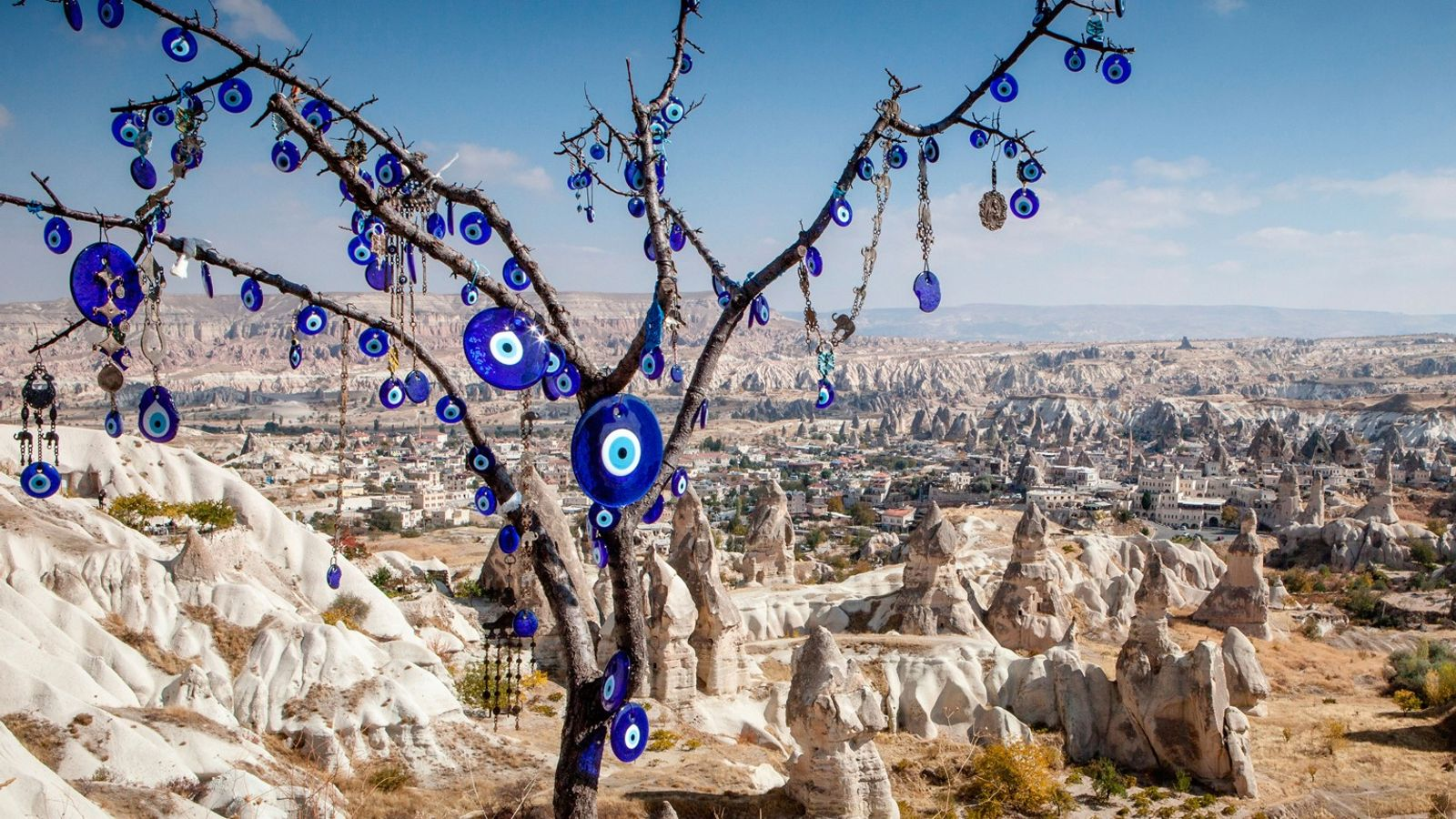 Outside Cappadocia, Turkey, blue glass evil-eye charms decorate a tree. The bad-luck repelling symbols are displayed ...