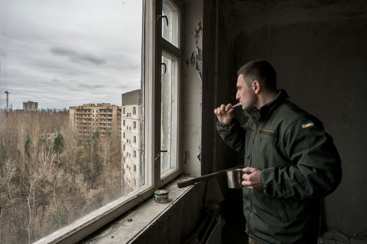 "Rudyavsky brushes his teeth in an apartment overlooking Pripyat. ""When you get to the zone, time ..."