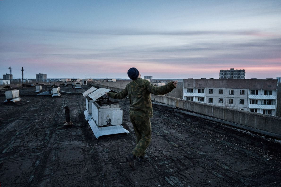 A stalker dances on a rooftop in Pripyat at sunset.