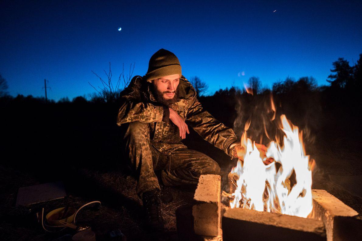 Knyazev prepares dinner in the abandoned village of Rudnya Veresnya.