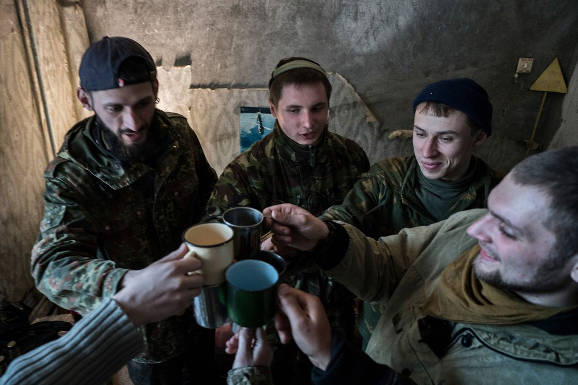 A group of stalkers enjoy a vodka party in Knyazev's zone apartment.