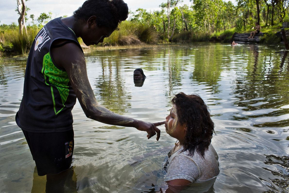 Girls paint their faces using clay from the creekbed at a swimming spot favoured by islanders.