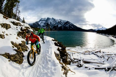A woman and man enjoy a winter fat bike ride in Banff National Park, Alberta.