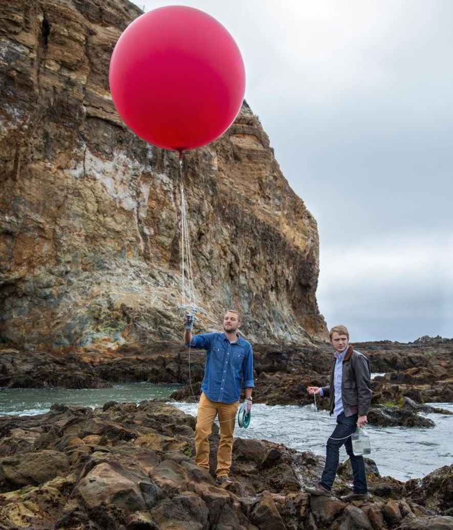 Shah Selbe (at left) and assistant Aaron Grimes use a balloon rigged with a camera to ...