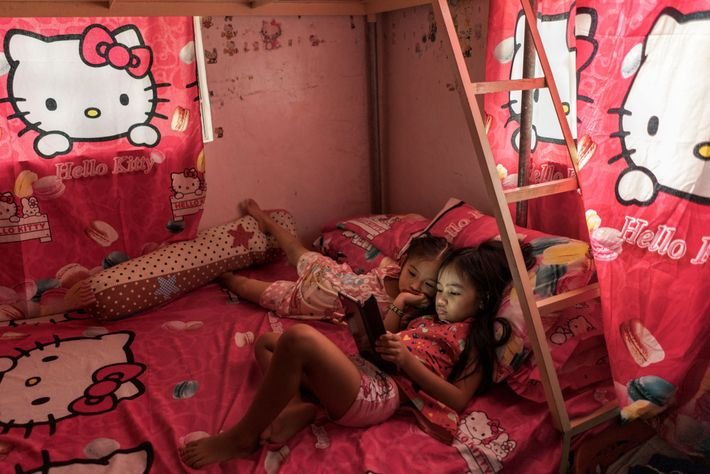Althea Tolidanes, eight, watches videos amid gifts of sheets, pillows, and curtains from her father, Arjay, ...