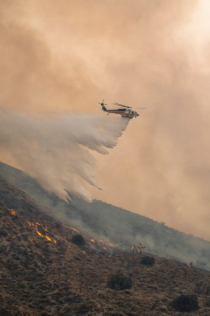 A Los Angeles County Firehawk helicopter drops water on the northern flank of the Bobcat Fire ...