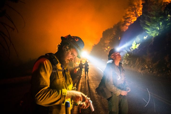 A firefighter reloads a flare gun at the Bobcat Fire in September. Firefighters shoot what they ...