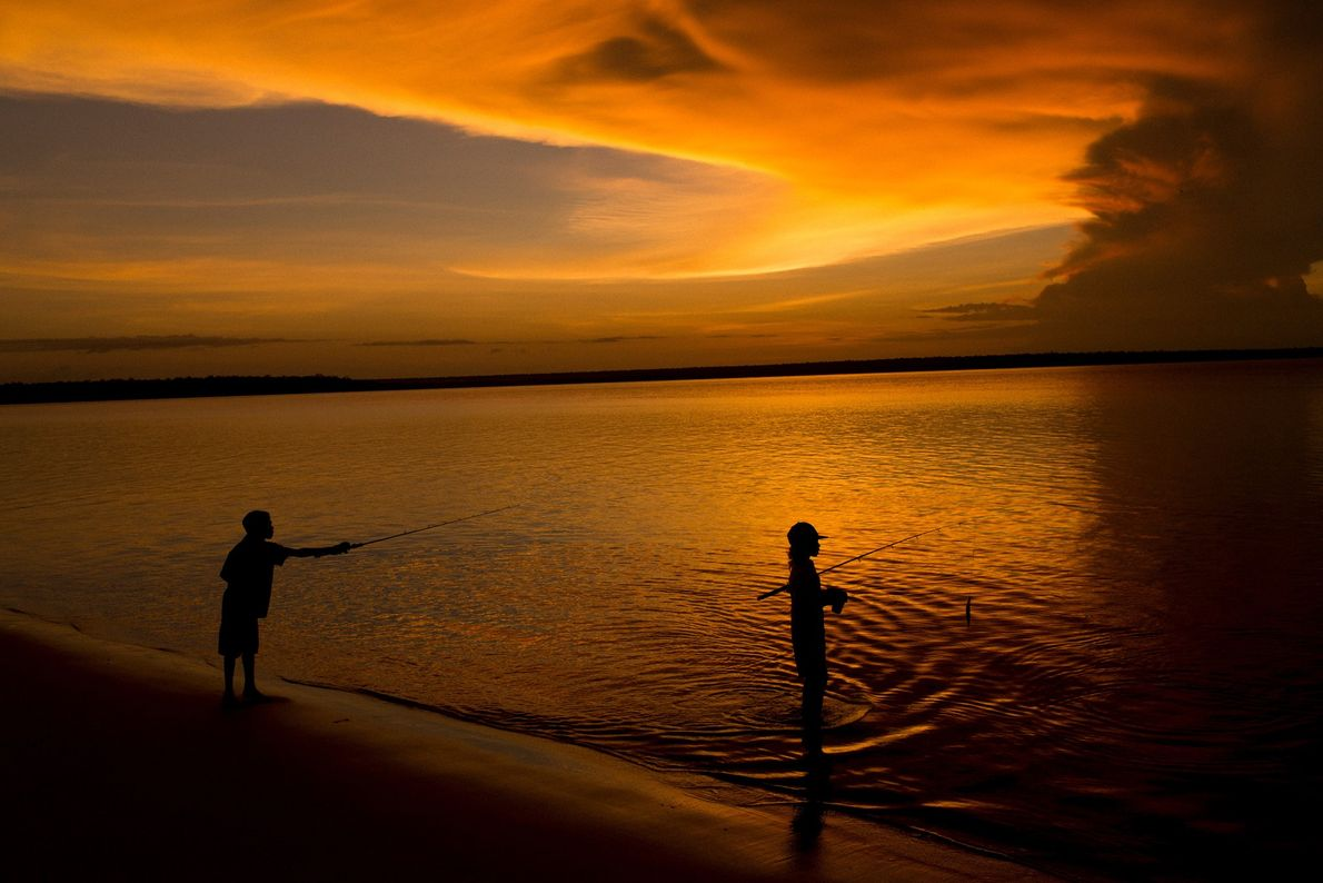 Young boys fish in the sea as a storm cell builds off the coast of Melville ...