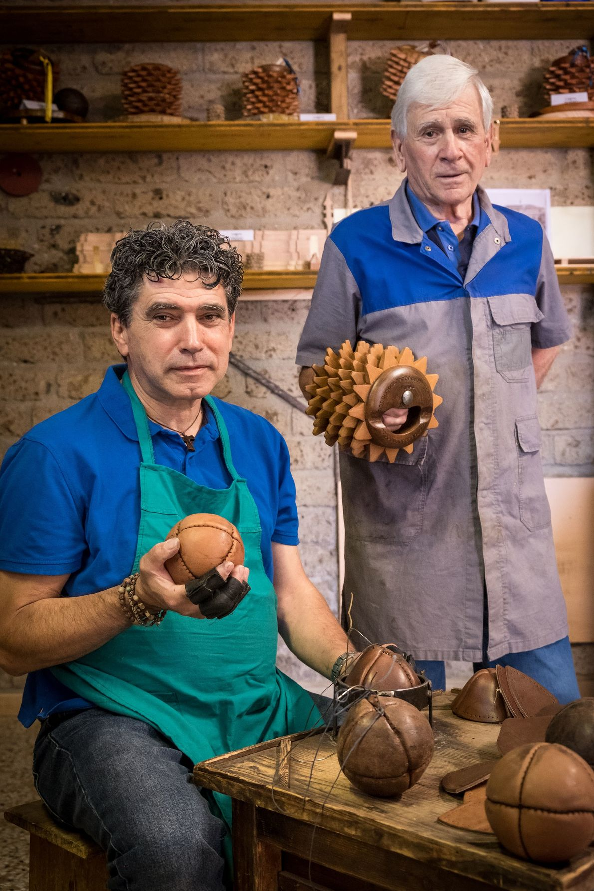 Craftsmen Daniele Rango (left) and Nazareno Crescimbeni (right) pose in their workshop with leather bracciale balls.