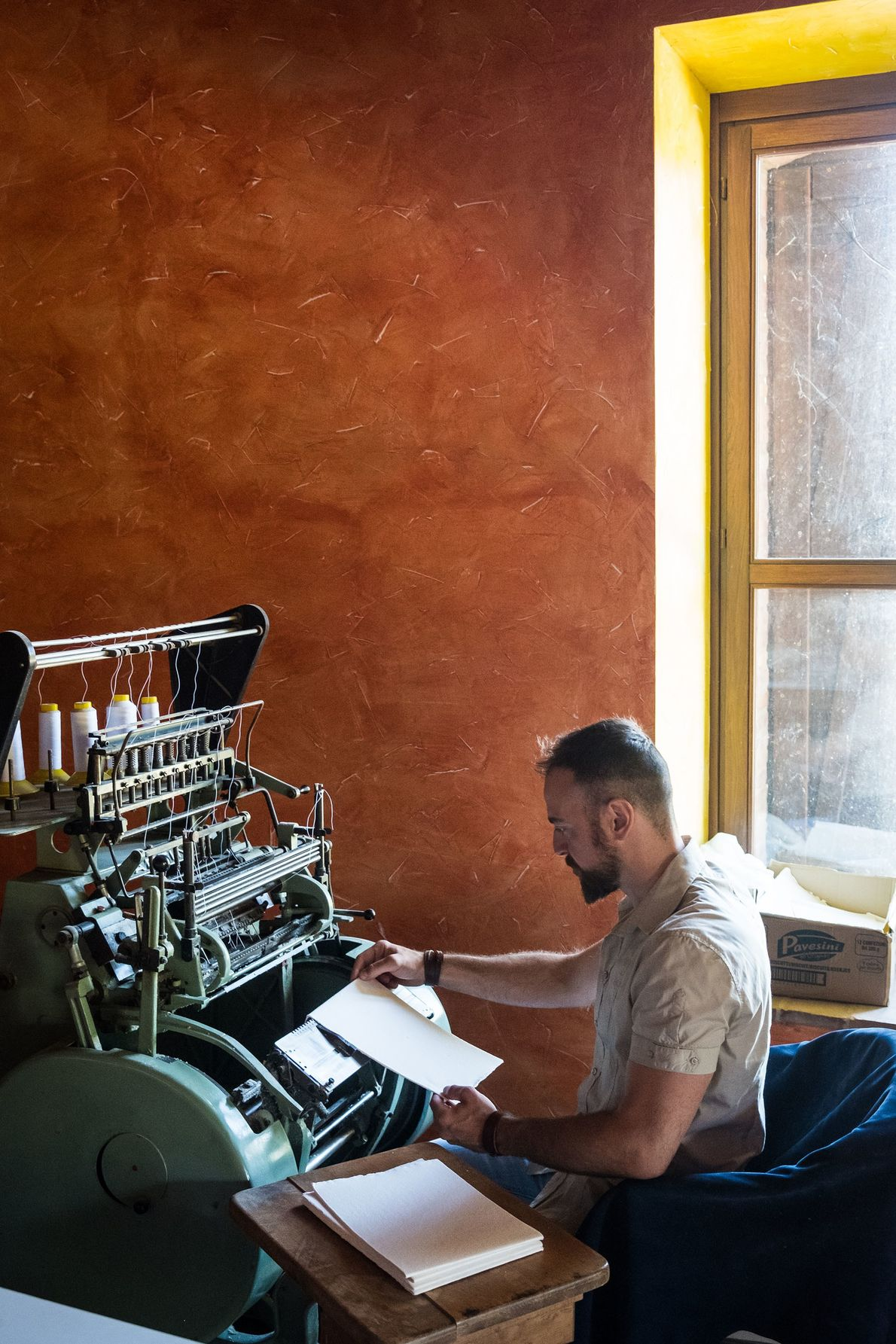 Craftsman Emiliano Scattolini at work binding books by hand in the workshop he shares with Luigi ...