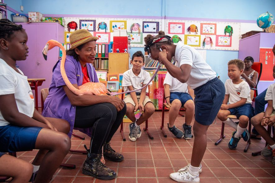 Rihantely Niles, then eight, listens to Bob's heartbeat at a school in Willemstad. The island's American ...