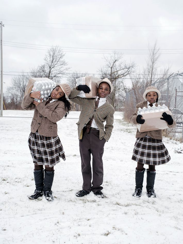 In Flint, Michigan, siblings Julie, Antonio, and India Abram collect their daily allowance of bottled water ...