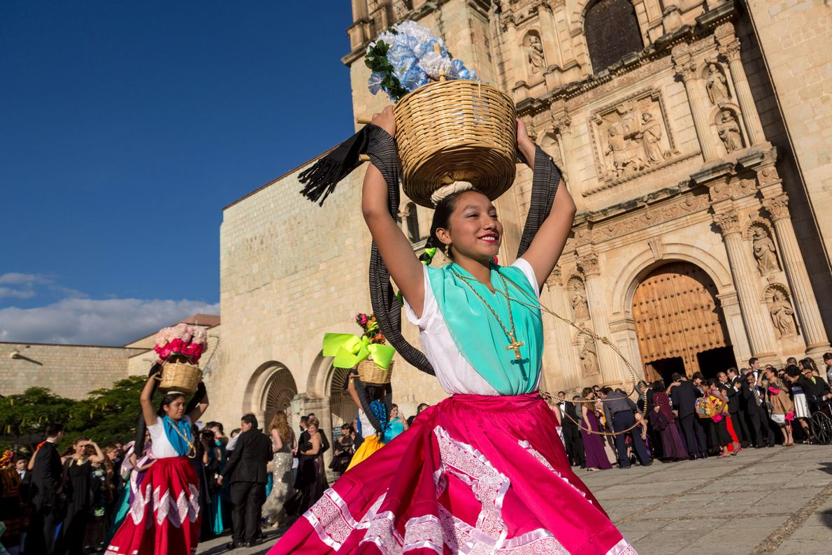 Dancers in traditional costumes perform in front of the Santo Domingo church in Oaxaca, Mexico.