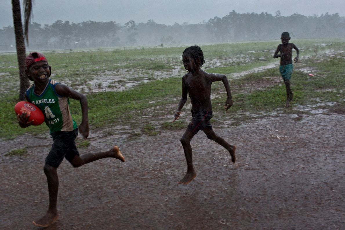 """Young boys play """"footy"""" during a rain storm in the community of Pirlangimpi. Australian rules football ..."""