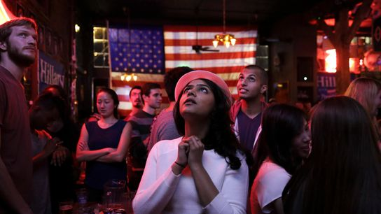 Young people watch news coverage of the 2016 presidential election results from a tavern in Seattle, ...