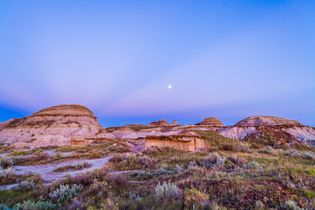 Gibbous moon and crepuscular rays over Dinosaur Provincial Park, Alberta, Canada.