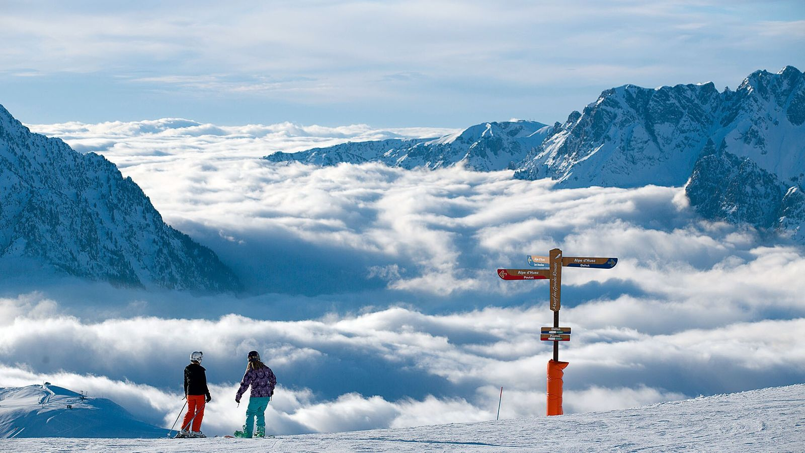 Skiiers stop to catch their breath while taking in a view of the Grandes Rousses massif from ...