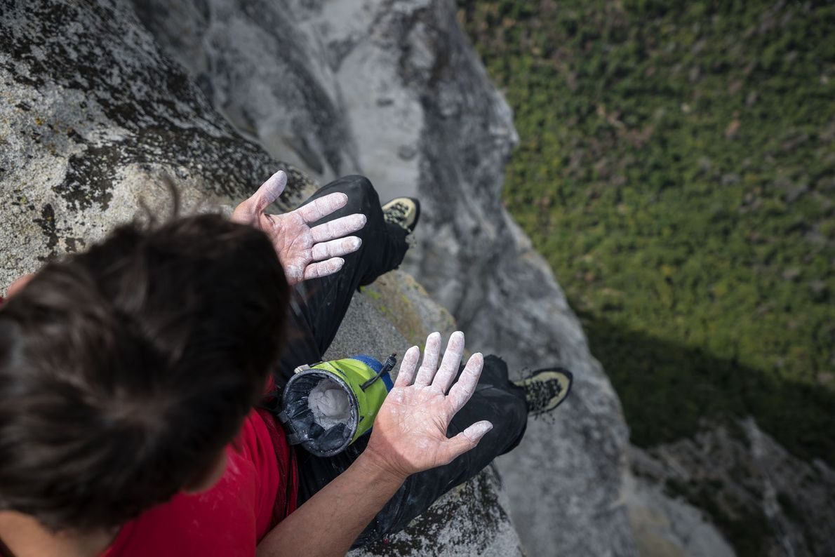 Honnold looks down at his chalked hands while sitting at the summit of Freerider on Yosemite's ...