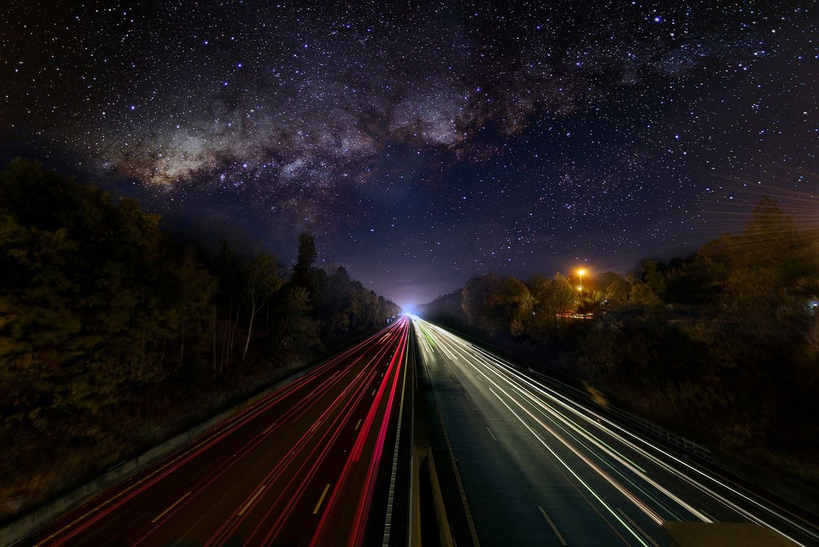 The band of the Milky Way shines over a busy highway in this long-exposure image.