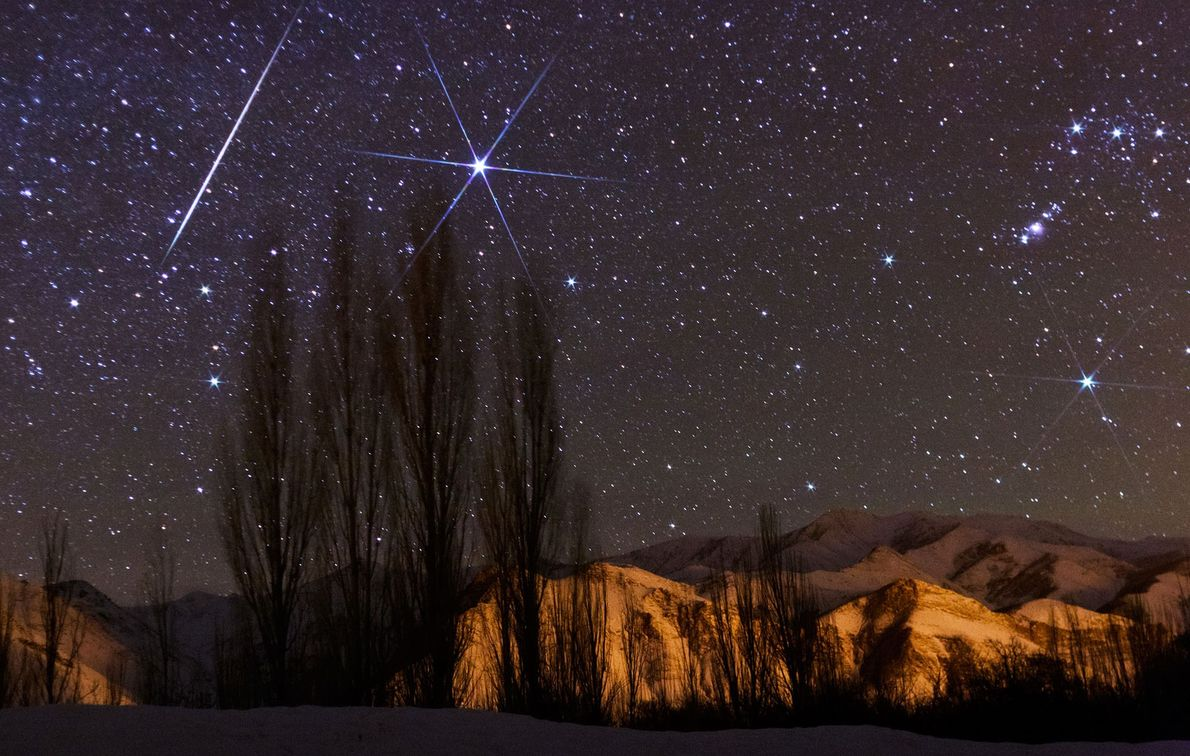 A bright meteor streaks the sky near Sirius during the Geminid meteor shower peak.