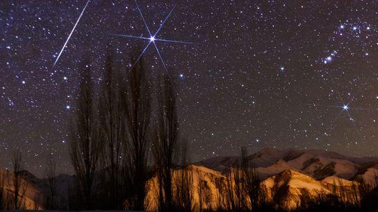 A bright meteor streaks the sky near Sirius during the Geminid meteor shower peak.