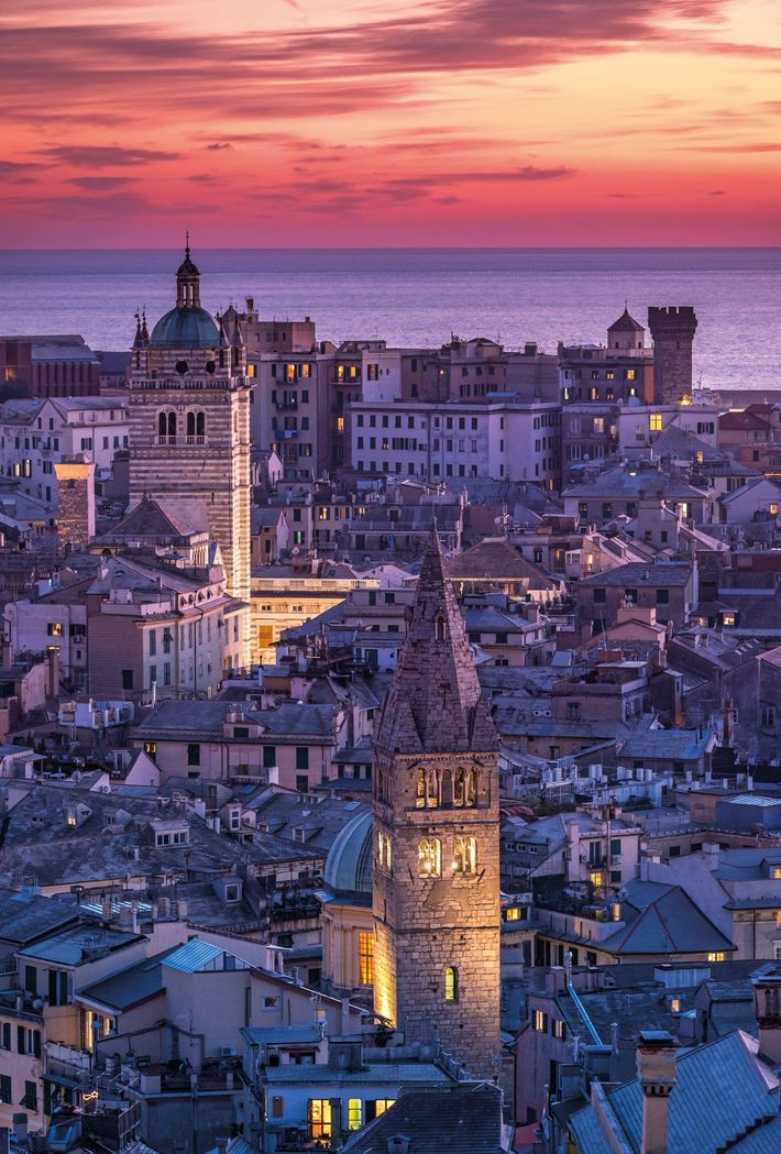 The tower (center left) of the 12th-century Cathedral of San Lorenzo rises over the Mediterranean port ...