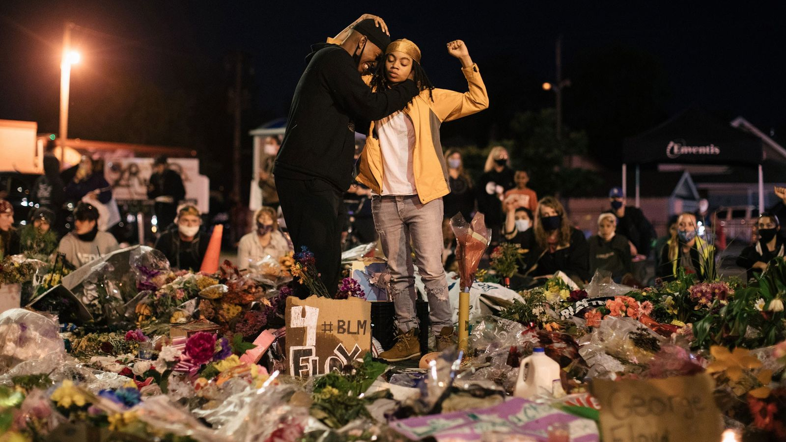 A woman raises her fist while comforting a grieving man at the place in Minneapolis where ...