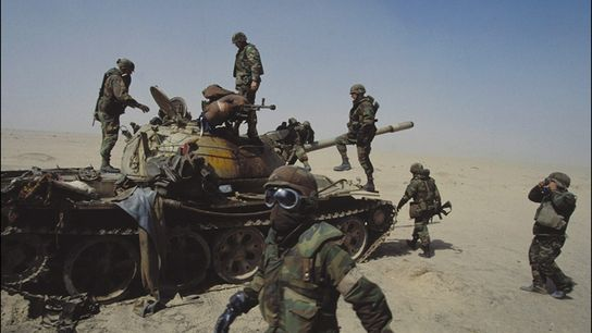 U.S. soldiers examine an Iraqi tank destroyed in February 1991, when 35 nations joined forces to ...