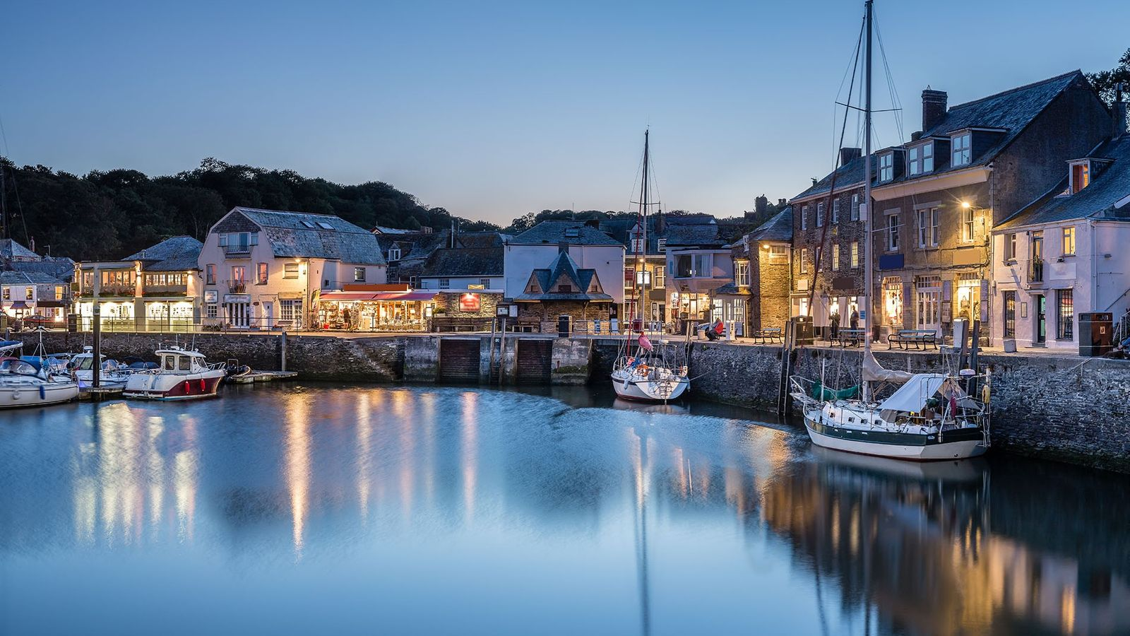 Padstow Harbour at blue hour, Cornwall, with reflections of the boats and lights in and around ...