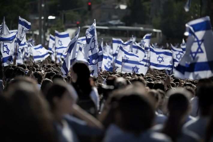 Israeli nationalists wave their nation's flag during a 2011 march through the streets of Sheikh Jarrah, ...