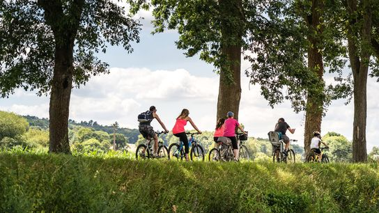 Here agroup of cyclists, both adults and children, rides along a canal in Brittany, France