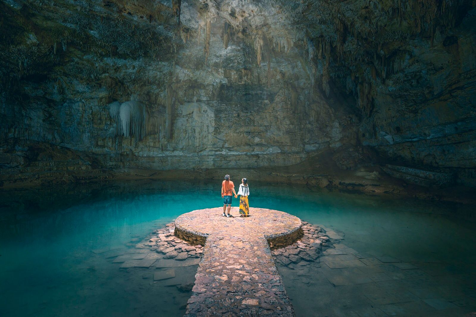 A couple holdhands while exploring a cenote in Mexico's Yucatán Peninsula.