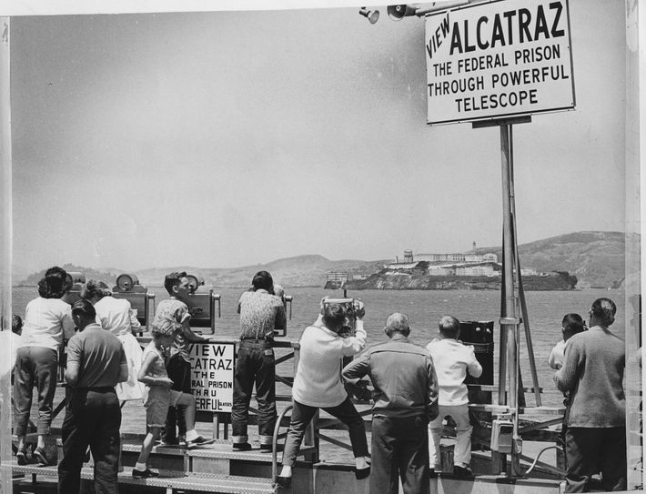 In this 1962 photo, people view Alcatraz through telescopes after a June escape attempt later made ...