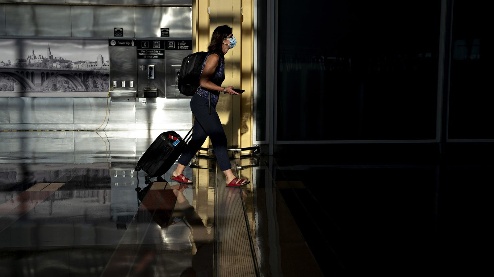A traveller in a face mask walks through Ronald Reagan National Airport in Arlington, Virginia on ...