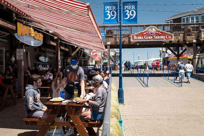 A masked server delivers food to patrons at a restaurant at San Francisco's Fisherman's Wharf on ...