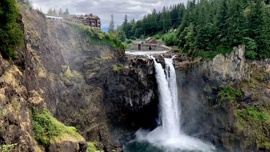 Waterfall east of Seattle, WA, with lodge in the background on a cloudy day. The lodge ...