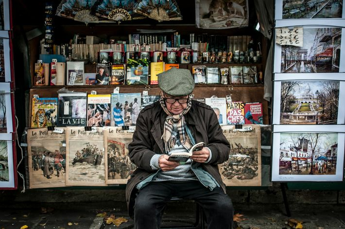A Parisian bouquiniste (bookseller) reads outside his stall, which sells used and antiquarian books, on the banks ...