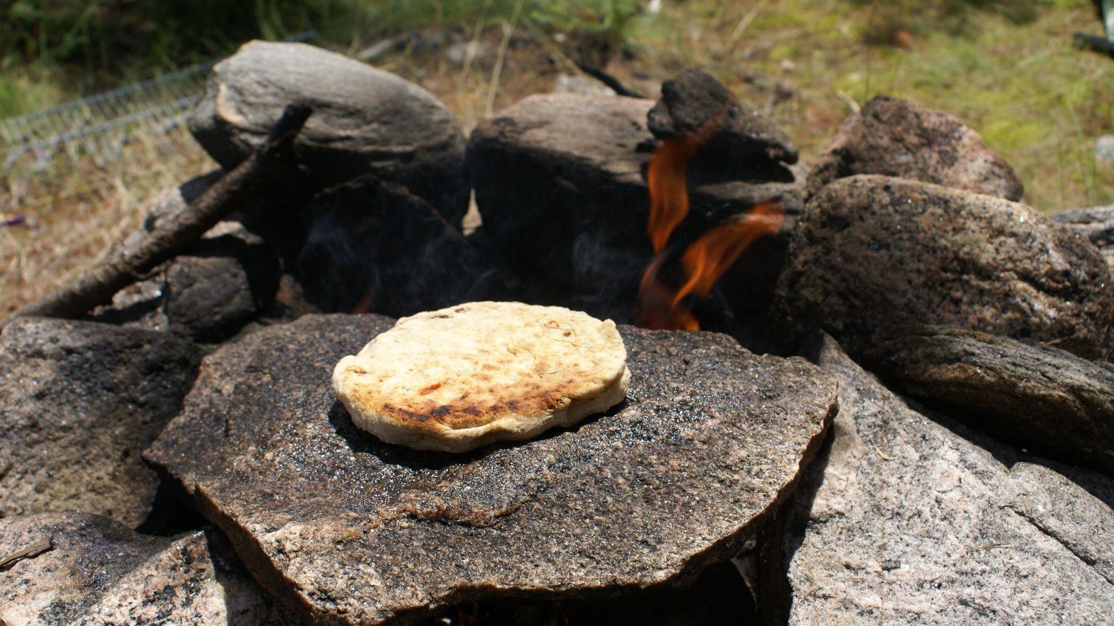 Bannock bread baked on a hot rock over a campfire.