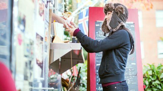 A young woman looks at a menu at a food cart pod in Portland, Oregon