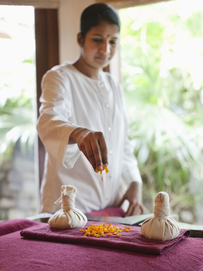 Spa Therapist prepares for the Choonaswedna Treatment, an ancient Ayurvedic practice that involves the application of ...